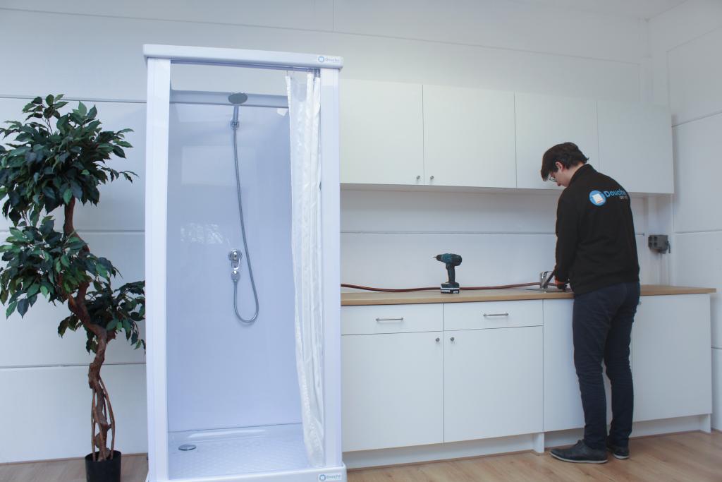 Service engineer tijdens de installatie van de tijdelijke douche